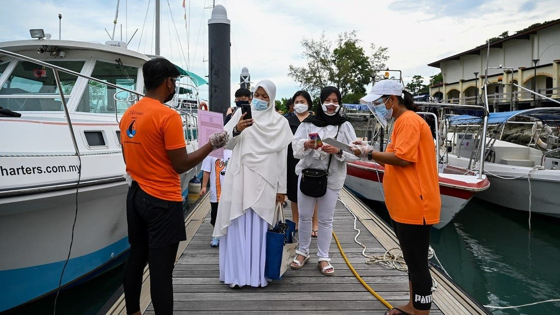 Passengers scan the MySejahtera app, used to monitor the Covid-19 coronavirus status, before boarding a catamaran yacht in Langkawi on September 17, 2021, as the holiday island reopened to domestic tourists following closures due to Covid-19 restrictions. (AFP)