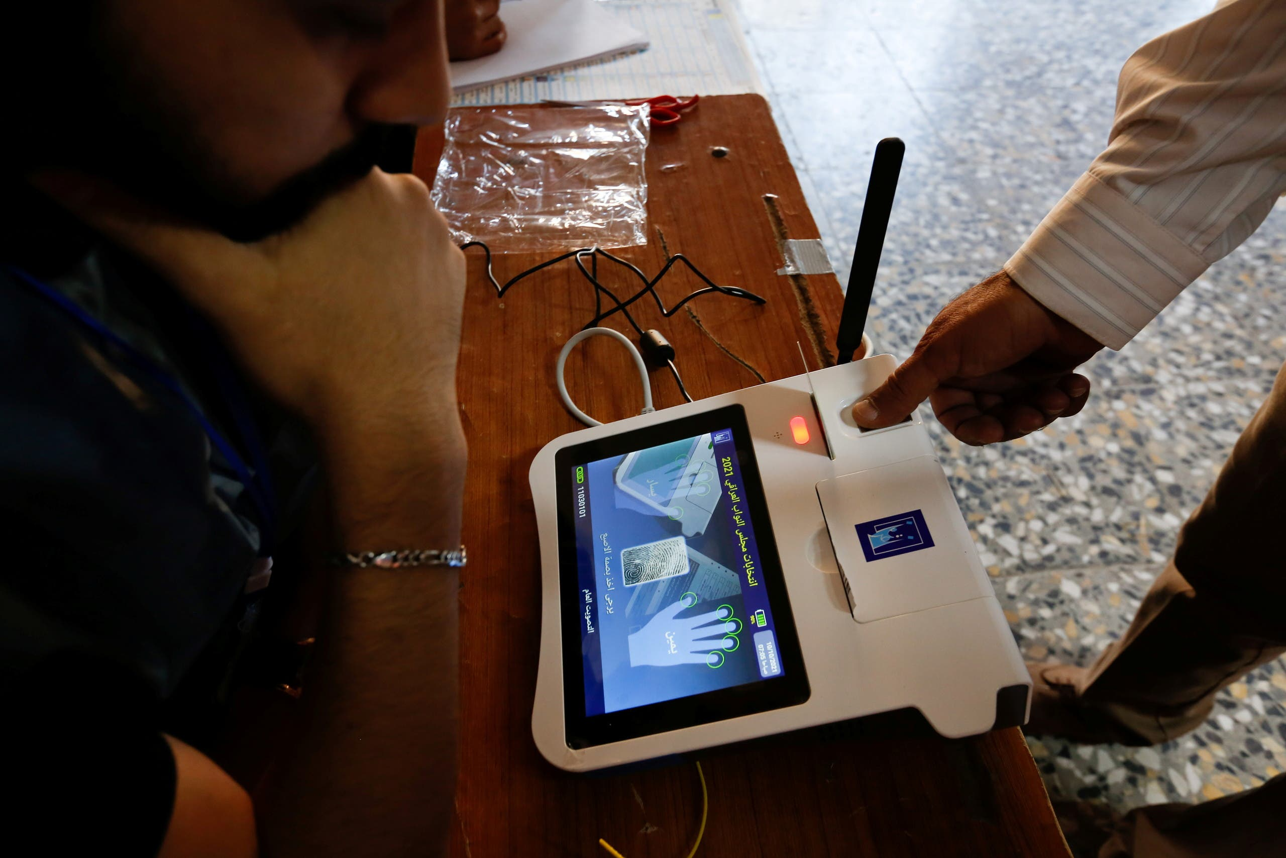 The finger of an Iraqi election official opens a device to start the legislative elections in Iraq, in Sadr City, Baghdad, October 10, 2021. (Reuters)