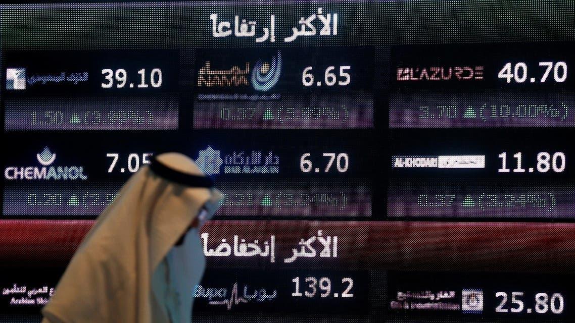 An investor walks past a screen displaying stock information at the Saudi Stock Exchange (Tadawul) in Riyadh, Saudi Arabia. (File photo: Reuters)