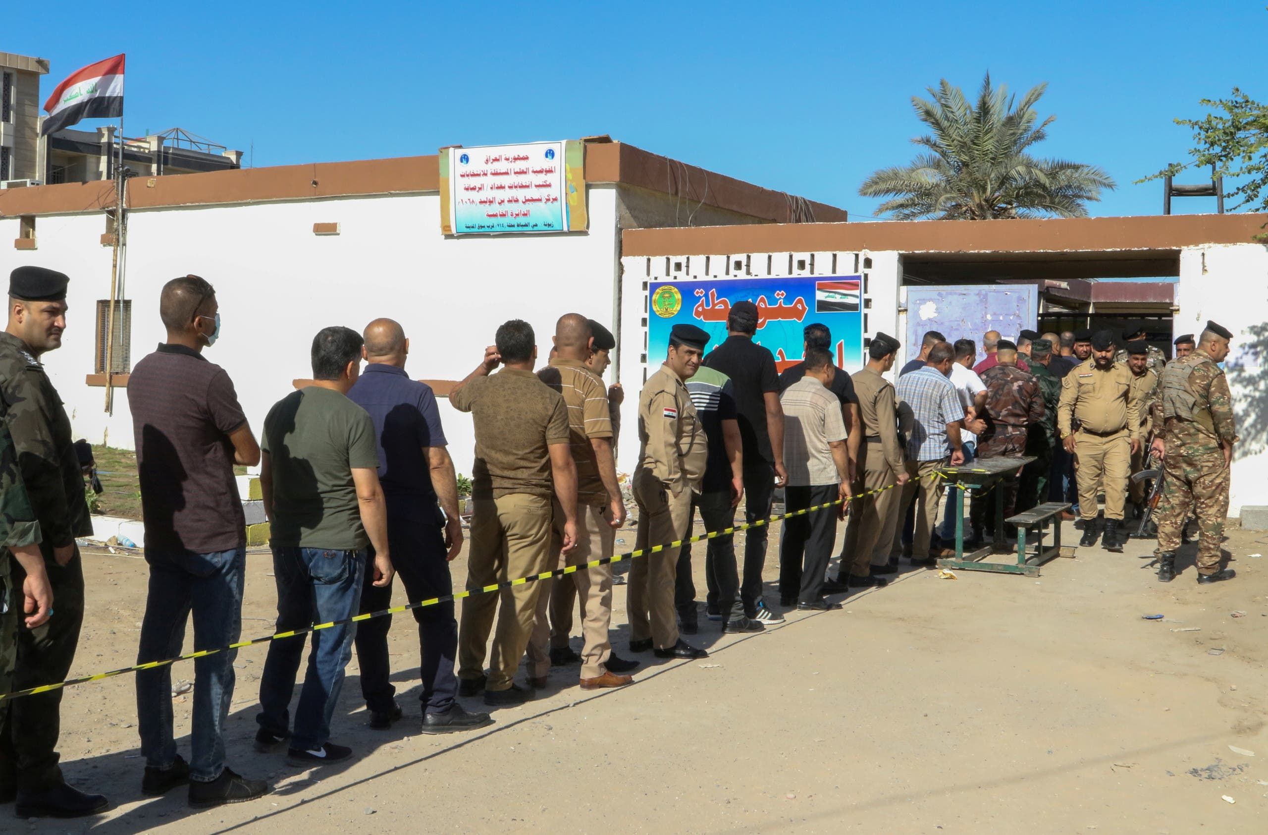 Members of Iraqi security forces line up outside a polling station waiting to cast their vote in a special process, two days ahead of Iraq's parliamentary elections, in Baghdad, Iraq October 8, 2021. (Reuters)