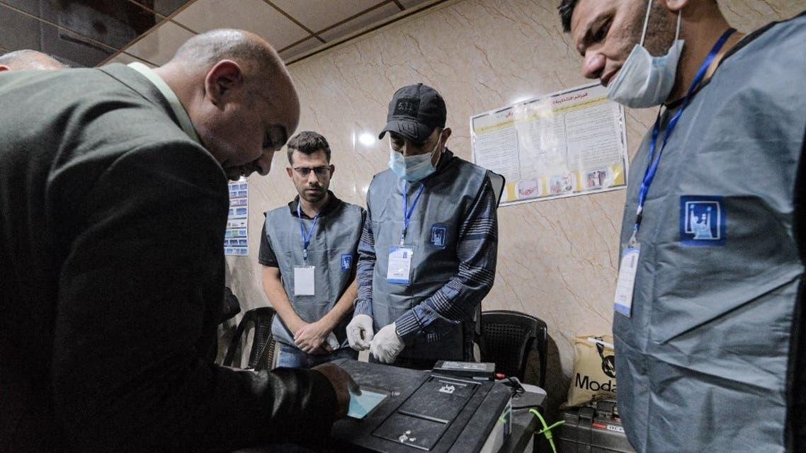 مسؤولو الانتخابات العراقيون يجرون الفرز الإلكتروني للأصوات في مركز اقتراع في مدينة الموصل