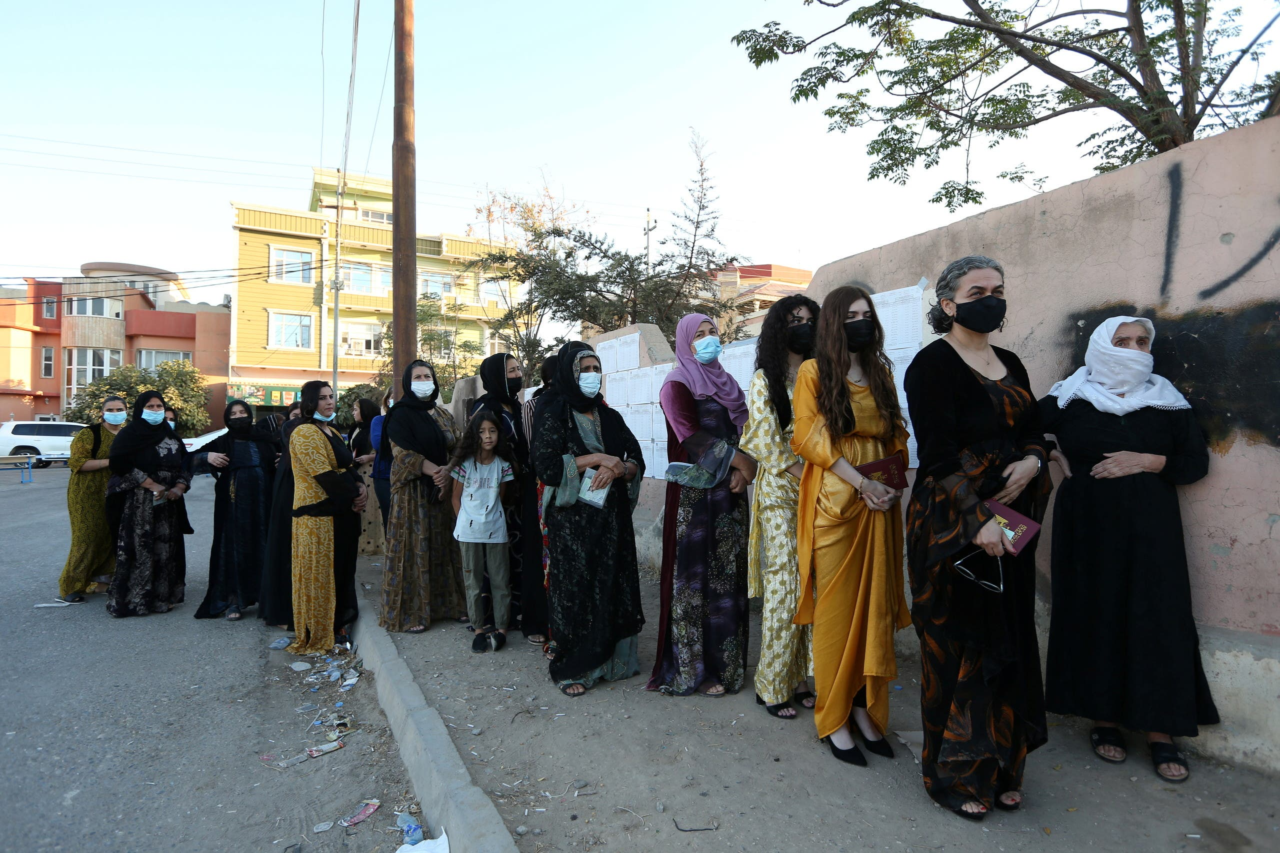 Voters stand in line at a polling station in Duhok, Iraq, October 10, 2021. (Reuters)