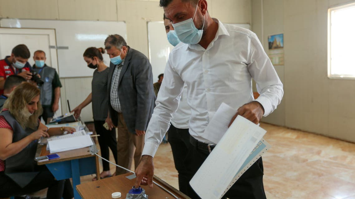 Darwesh Khodeda Hassan, a displaced Yazidi man, casts his vote at a polling station, two days ahead of Iraq's parliamentary elections in a special process, at the Sharya camp in Duhok, Iraq, October 8, 2021. (Reuters)