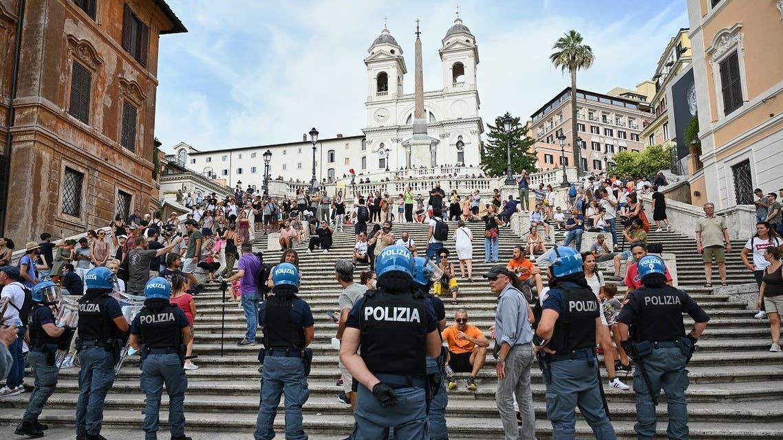 """Protestors stand in front of riot police officers during a demonstration against the introduction of a mandatory green pass in the aim to limit the spread of the Covid-19, called by far right Forza Nuova party activists and Io Apro"""" (I open up) group of restaurant owners and workers, entrepreneurs and small businesses owners on July 27, 2021 at Piazza di Spagna by the Spanish Steps, below the Trinita dei Monti church, in Rome. (AFP)"""