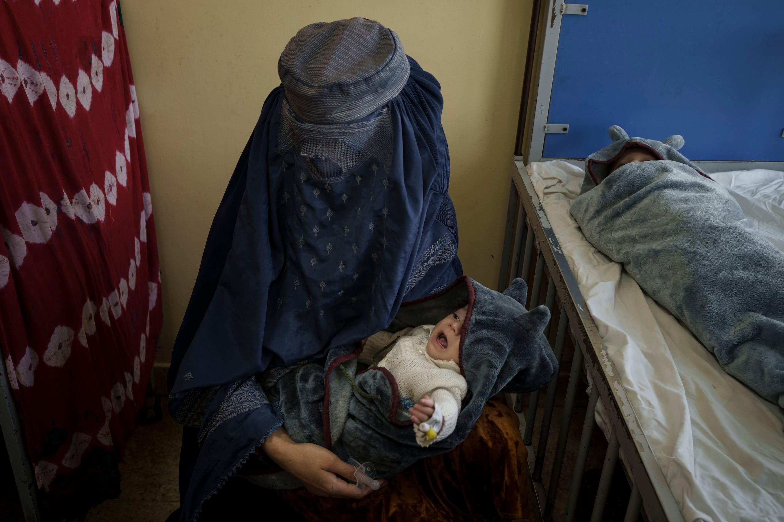 A woman holds one of her two babies undergoing treatment at the malnutrition ward of the Indira Gandhi Children's Hospital in Kabul, Afghanistan, Tuesday, Oct. 5, 2021. (AP)