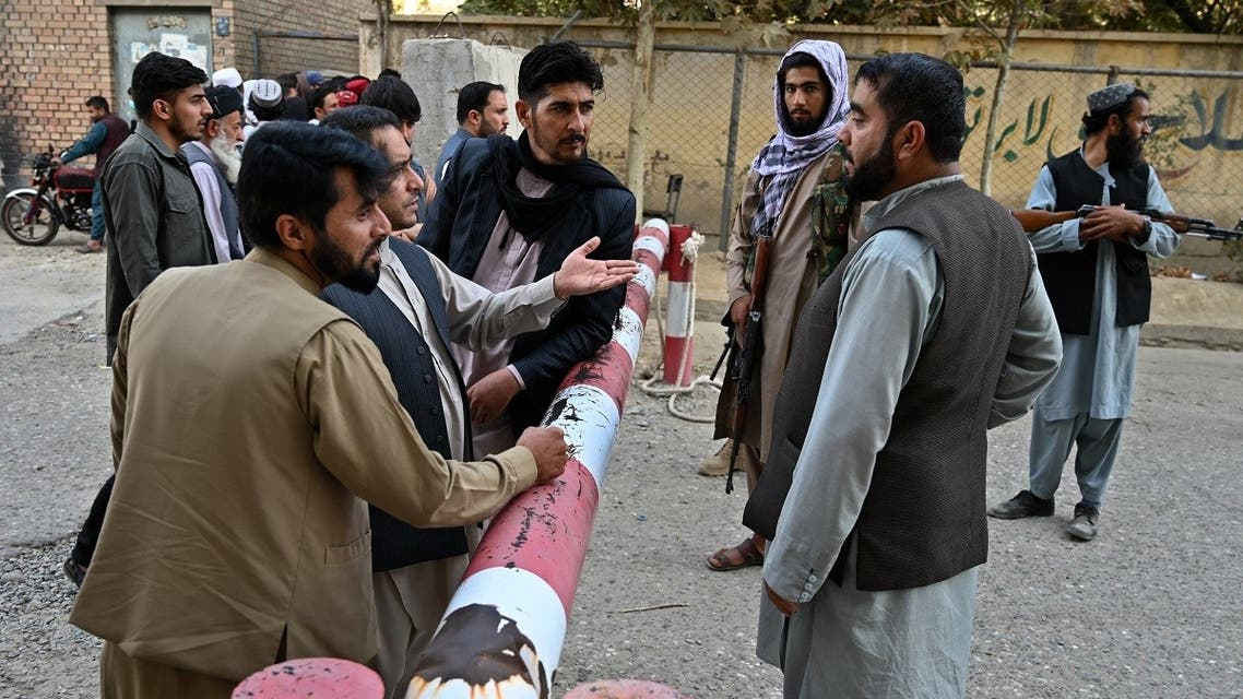 Taliban fighters stand at a gate as people wait with their documents after Taliban announced the reopening for passport applications, outside the passport office in Kabul on October 6, 2021. (AFP)