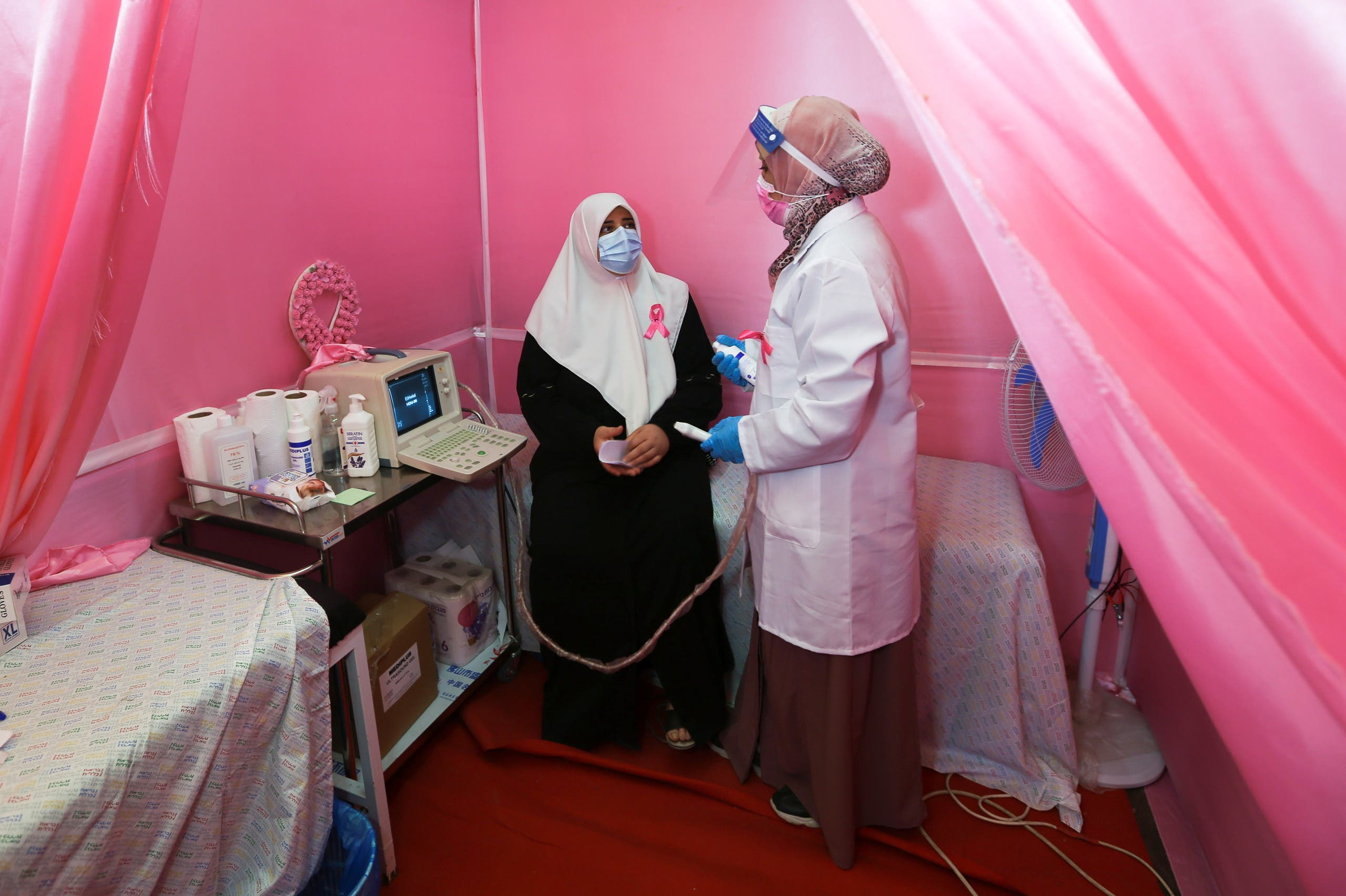A Palestinian doctor prepares a woman for a breast cancer check up inside a mobile clinic set up in a truck, during a campaign aimed to raise public awareness in Gaza over the need for early tests to discover breast cancer, in Khan Yunis, in the southern Gaza Strip, October 7, 2021. (Reuters)