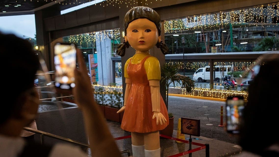 """People take pictures of the 3-meter (10 ft) tall doll from Netflix series """"Squid Game"""" displayed outside a mall in Quezon City, Philippines. (Reuters)"""
