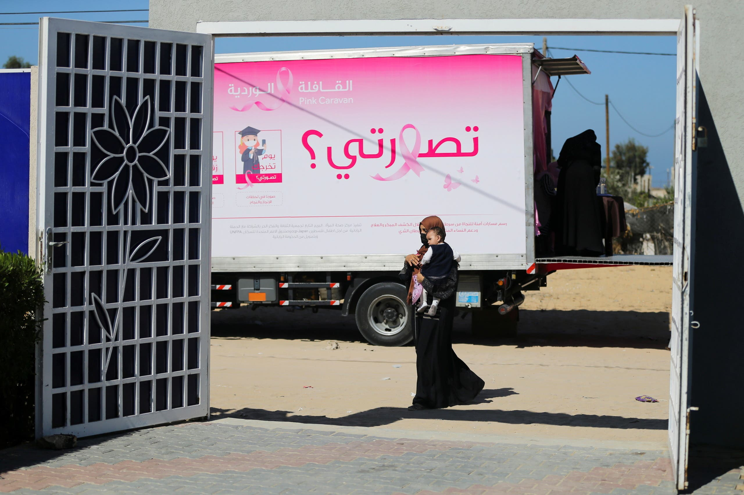 A Palestinian woman leaves a mobile clinic set up in a truck after a breast cancer check up, during a campaign aimed to raise public awareness in Gaza over the need for early tests to discover breast cancer, in Khan Yunis, in the southern Gaza Strip, October 7, 2021. (Reuters)