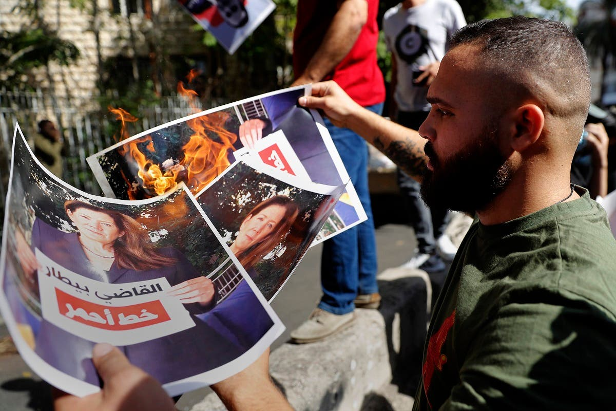 مناصرون لحزب الله وحركة أمل يحرقون صور السفيرة الأميركية ببيروت رافعةً لافتة تأييد للبيطار خلال مظاهرة الخميس