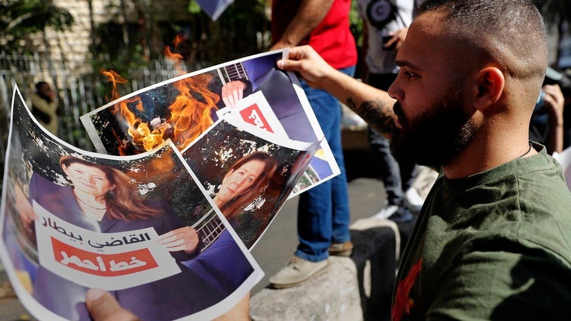 Supporters of Hezbollah and the Amal movement burn a portrait of Judge Tarek Bitar, the Beirut blast lead investigator, and US Ambassador to Lebanon Dorothy Shea near the Justice Palace, Oct. 14, 2021. (AFP)