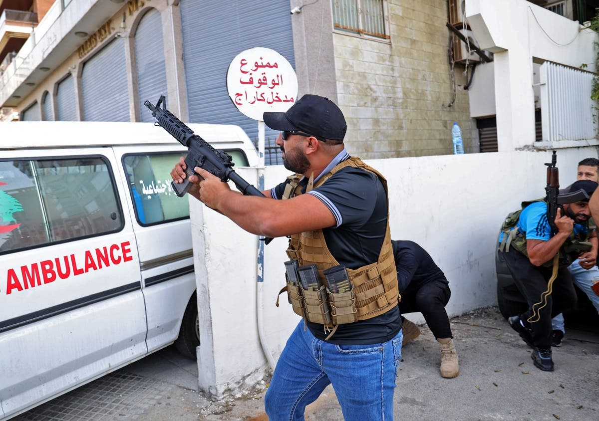 A fighter from the Amal movement takes aim during clashes in the area of Tayouneh, in the southern suburb of the capital Beirut, on October 14, 2021. (AFP)