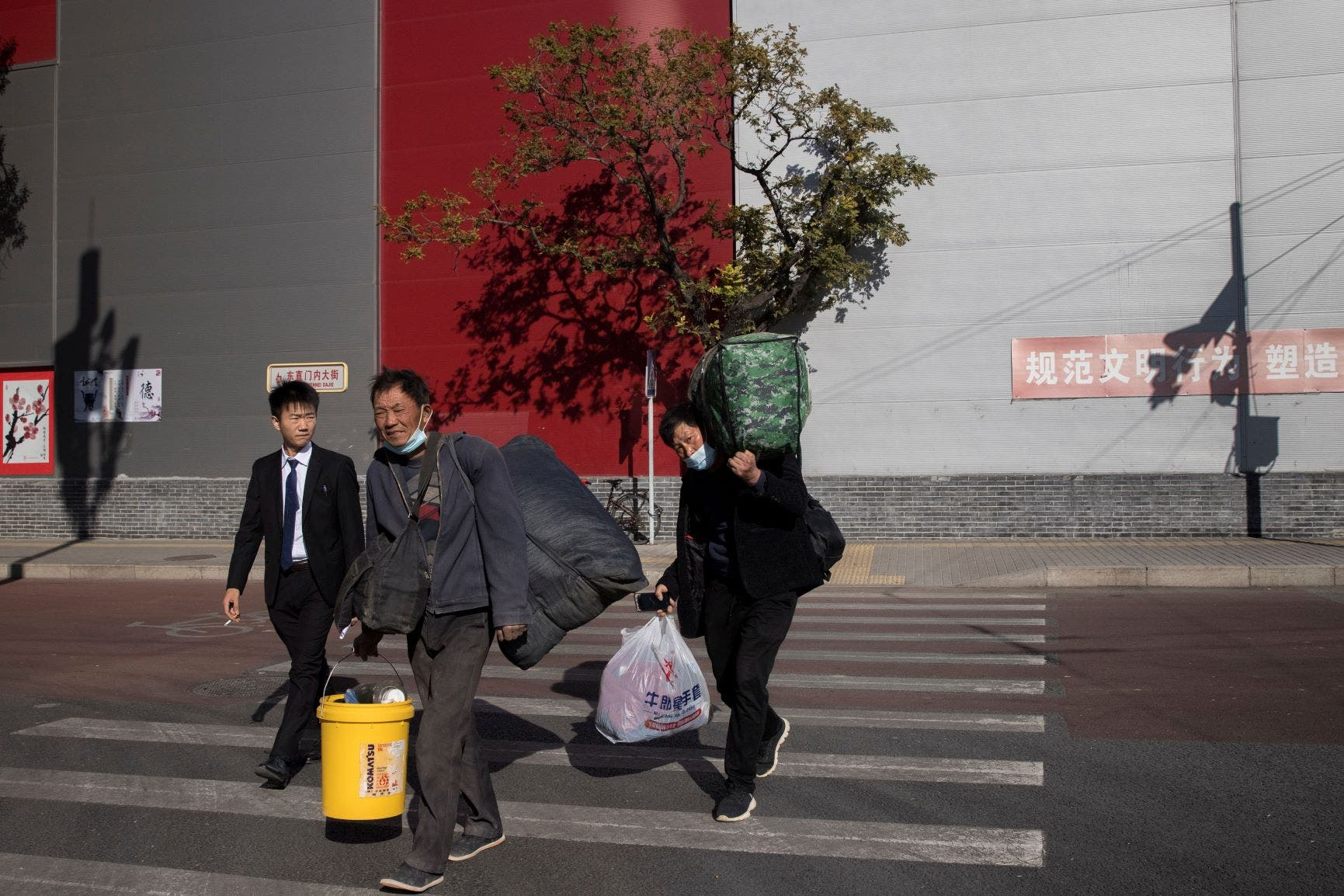 Workers and a businessman cross a street during morning rush hour following an outbreak of the coronavirus disease (COVID-19) in Beijing, China, November 3, 2020. (Reuters)