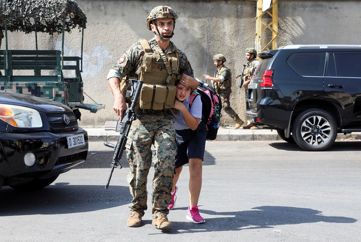 An army soldier helps a schoolgirl get to her parents, after a gunfire erupted in Beirut, Oct. 14, 2021. (Reuters)