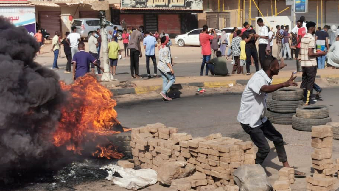 Sudanese protesters burn tyres to block a road in 60th Street in the capital Khartoum, to denounce overnight detentions by the army of members of Sudan's government, on October 25, 2021. (AFP)