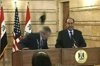 """صحفي عراقي يقذف بوش والمالكي بحذائه ويهتف قائلا: """"كلب"""""""