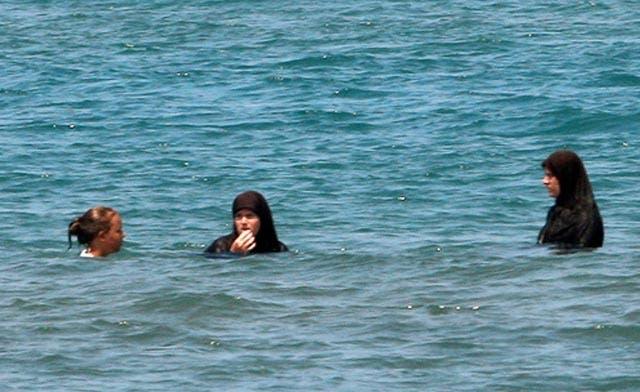 Bikinis and hijabs contrast on Albanian beach